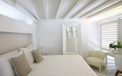 Bed, mirror & sofa in the bedroom area of the Semeli Hotel luxury Executive Jacuzzi Suite in Mykonos
