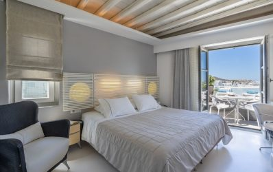 Double bed by the balcony overlooking the Mykonos town in Superior Double Sea View with Room Spa.