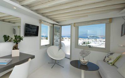 Καναπές, τραπέζι, γραφείο & πολυθρόνα στο σαλόνι της πολυτελούς Mykonos Executive Sea View Σουίτα