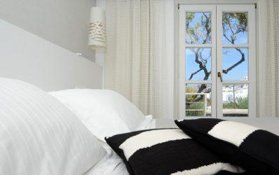 Μαξιλάρια σε κρεβάτι δίπλα σε μπαλκονόπορτες που οδηγούν στο αίθριο ενός πολυτελούς Mykonos Superior Double Garden View Δωματίου