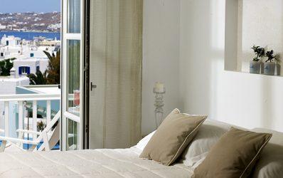 Κρεβάτι δίπλα σε παράθυρο βεράντας σε ένα από τα πολυτελή Semeli Hotel Mykonos Superior Double Sea View Δωμάτια