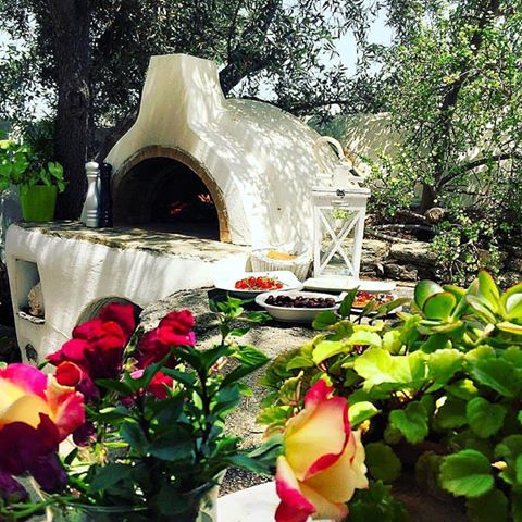 A traditional oven at a beautiful garden with trees and flowers in Mykonos.