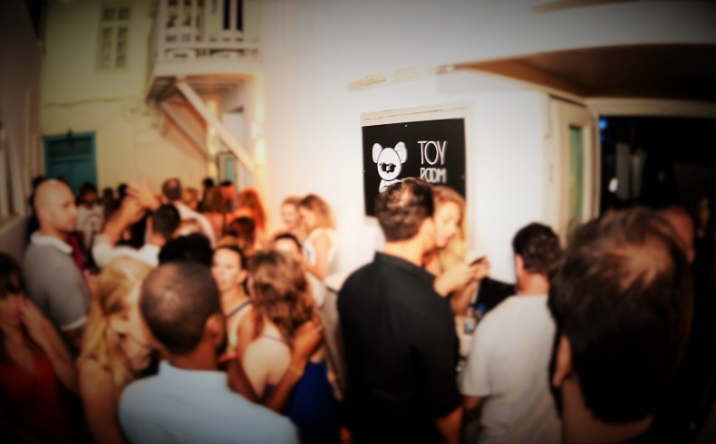 Tourists dancing by the entrance of Toy Room Mykonos Club, which belongs to Semeli Group.