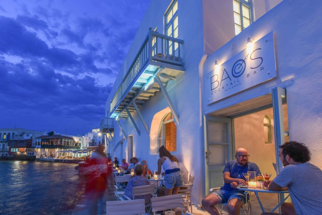 The entrance of Bao's bar, the bar by the sea in Mykonos. Visitors sitting outside, having a drink.