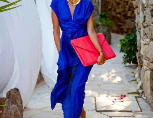A lady in a blue dress holding a red purse walking down a beautiful path in Mykonos.