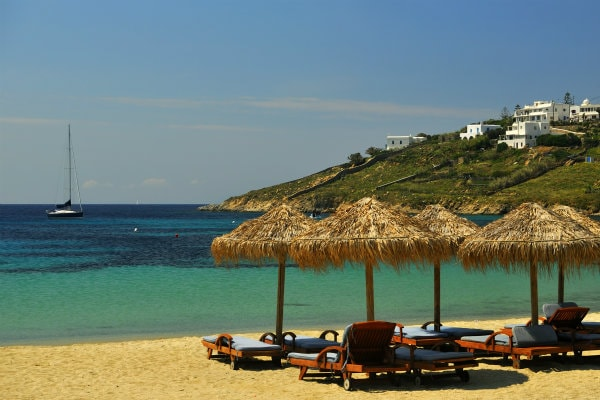 Sun umbrellas and sun loungers at a beach in Mykonos town overlooking the crystal clear sea.
