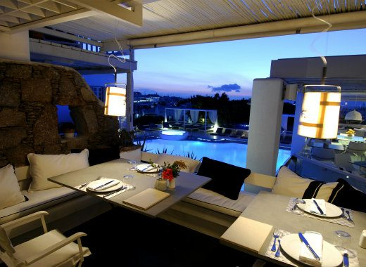 Dining tables and chairs at the restaurant in Semeli Luxury Hotel in Mykonos.