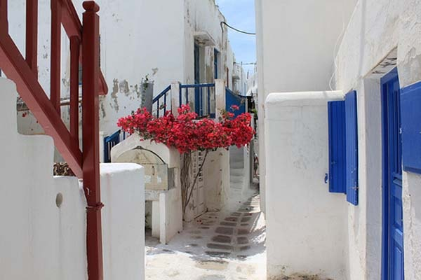 Beautiful path at Mykonos Town. Traditional houses and red flowers.