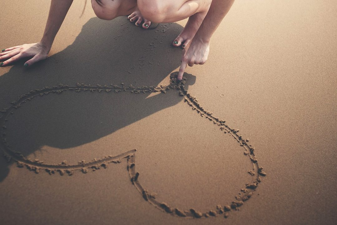 Young woman creating a heart on the sand at a beach of Mykonos, where Semeli Hotel is located.