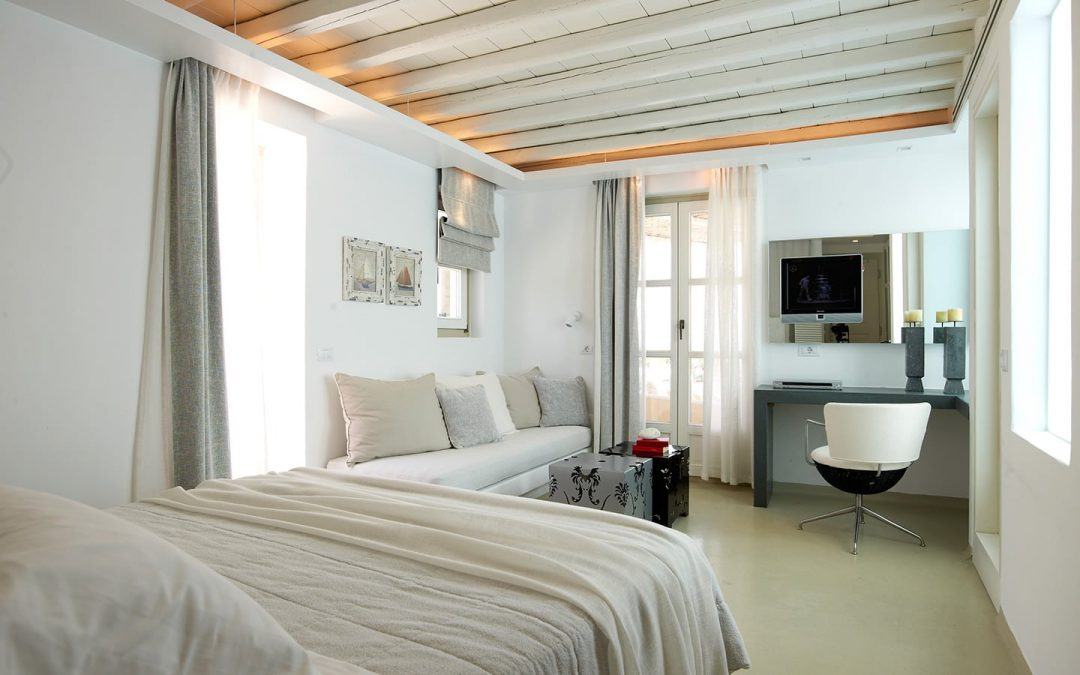 Double bed, built-in sofa and desk at Semeli Best Hotel in Mykonos.