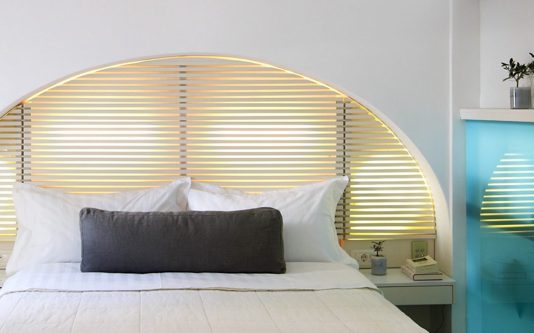 Double bed and an arched window at a suite in Semeli Luxury Hotel in Mykonos.