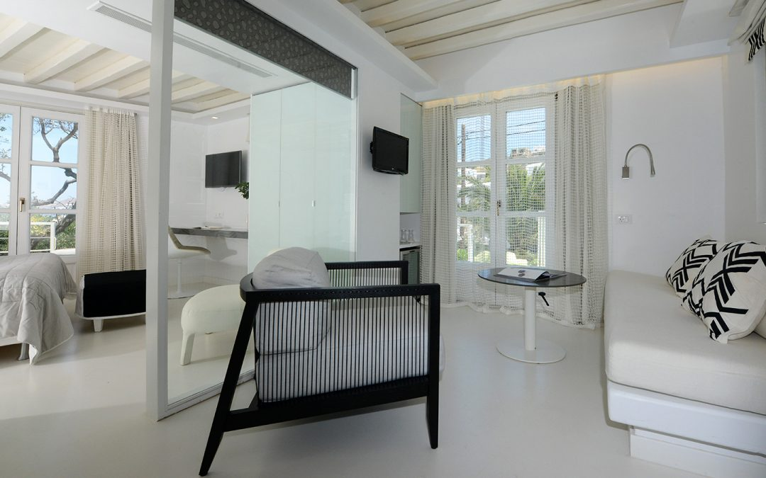 Built-in sofa, stylish armchair, and a round table at one of the suites in Semeli Hotel in Mykonos.