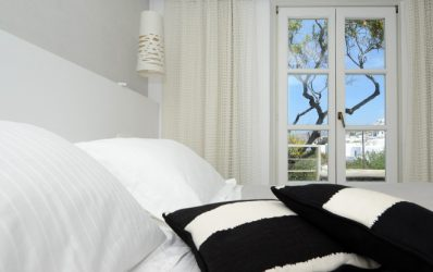 Pillows on bed by patio doors of luxury Superior Double Garden View Rooms accommodation in Mykonos