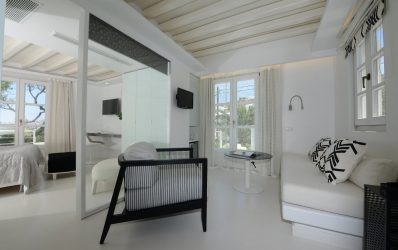 Junior Suite Double Sea View bedroom & living room with chair, sofa & table at Semeli Hotel, Mykonos